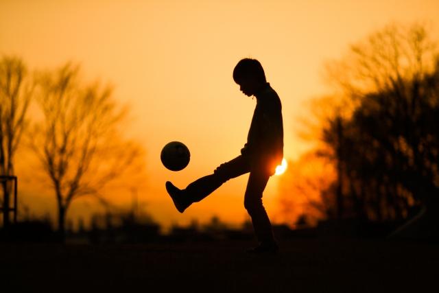 1人でサッカーをする子どものシルエット