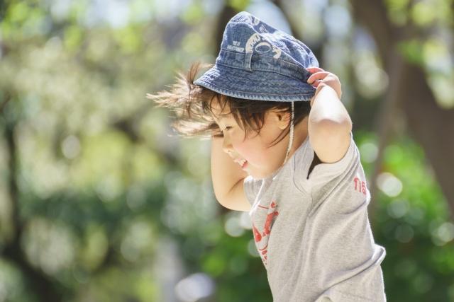 風で吹き飛びそうになる帽子を押さえる子供