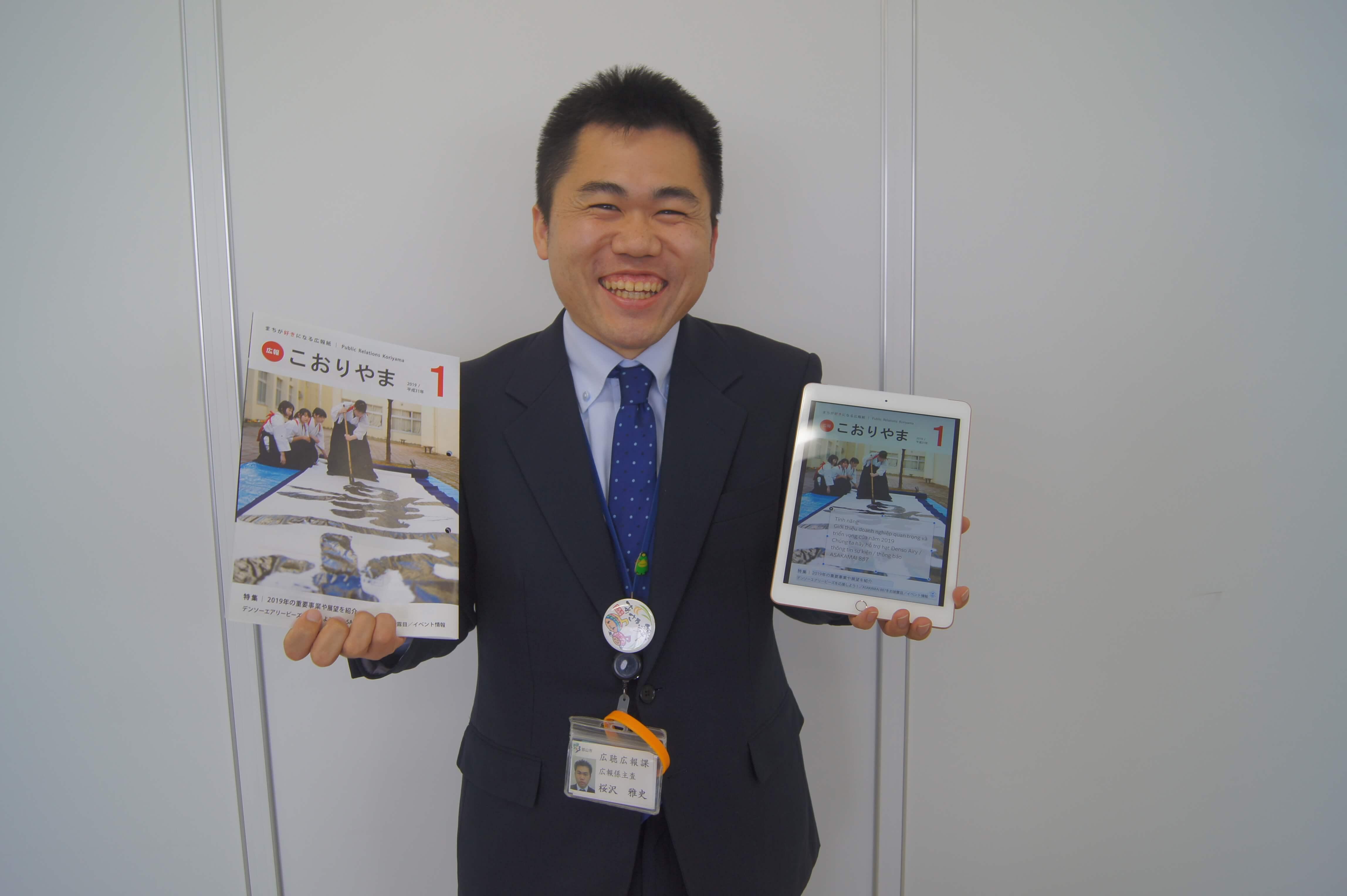 広報誌を手に取り説明する福島県郡山市の広報担当者