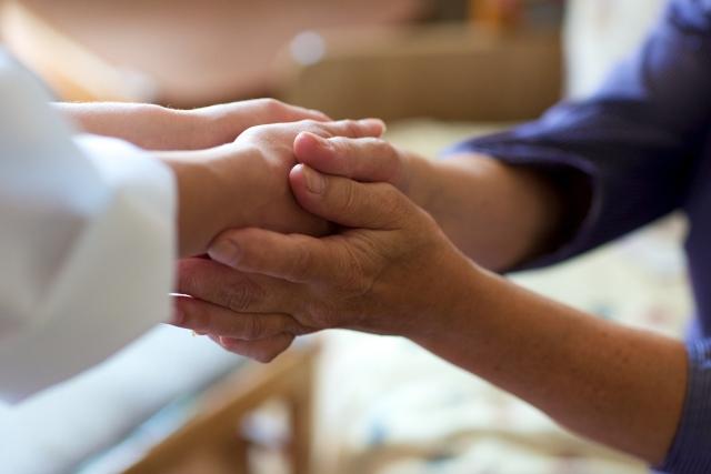 手を取り合う医療従事者と患者